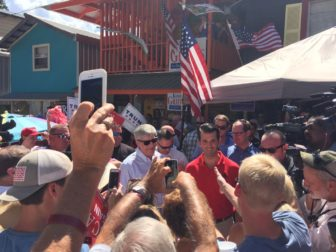 Gov. Phil Bryant, left, accompanies Donald Trump Jr. through the crowd of supporters at the Neshoba County Fair on Tuesday.