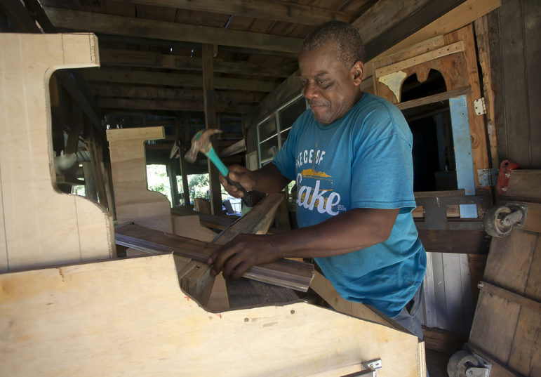 Folk artist Earl Simmons builds a wooden airplane recently at his work space in Warren County. Simmons said he hopes to rebuild after a massive fire destroyed the building in August of 2002.