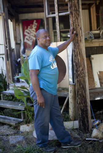 Folk artist Earl Simmons stands near the front porch of his art gallery which is being rebuilt after two massive fires destroyed the building.