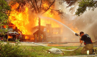 In August 2002, a Culkin Volunteer Firefighter rests his head while fighting a large fire at the home and gallery of folk artist Earl Simmons in Bovina.