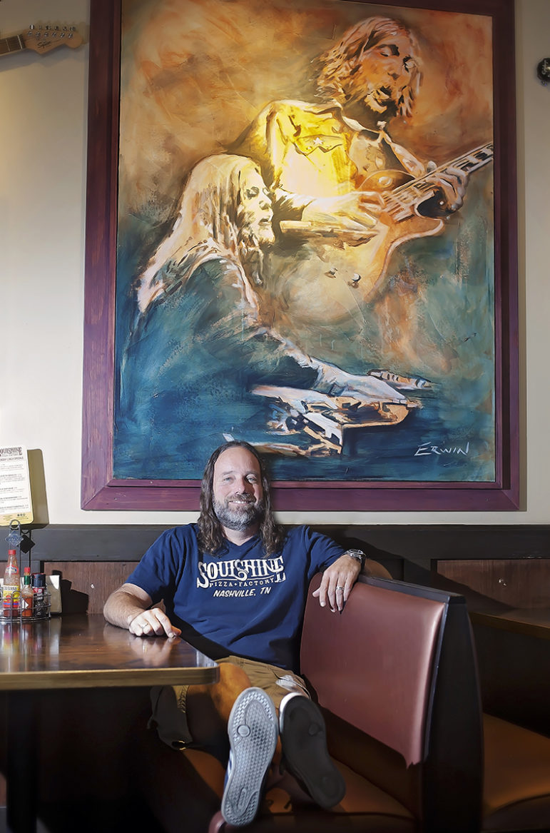 """Soulshine Pizza Factory owner Chris Sartin sits under one of the paintinga that helps set the tone at his chain of pizza restaurants, which he calls """"deer camp for hippies."""""""