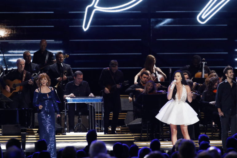 """Kacey Musgraves, center, performs """"Here You Come Again"""" in a medley tribute to Dolly Parton at The 50th Annual CMA Awards, live Wednesday, Nov. 2, at Bridgestone Arena in Nashville and broadcast on the ABC Television Network. Meridian native Benjamin Johnson, far right, was selected to sing back-up on the performance, which also featured Reba McEntire, far left."""