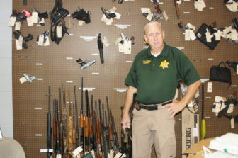 Monroe County Sheriff Cecil Cantrell in the evidence room with seized guns, including from local drug dealers.